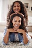Porträt der Tochter zurück liegend auf Müttern im Aufenthaltsraum stockfoto