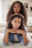 Porträt der Tochter zurück liegend auf Müttern und im Aufenthaltsraum aufwerfend lizenzfreies stockfoto