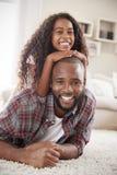 Porträt der Tochter zurück liegend auf Vätern im Aufenthaltsraum lizenzfreie stockbilder