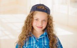 Porträt der tragenden Jungenkleidung blaues T-Shirt und Hut des schönen gelockten Mädchens lizenzfreie stockfotografie
