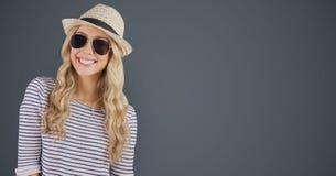 Porträt der tragenden Sonnenbrille des glücklichen weiblichen Hippies und des Sonnenhutes gegen grauen Hintergrund Stockbilder