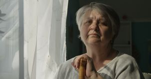 Porträt der traurigen älteren Frau, die zuhause das Fenster-Konzept der Krisen-Einsamkeit betrachtet stock video