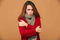 Porträt der traurigen einfrierenden Brunettefrau im Rot strickte Strickjacke s stockfotos