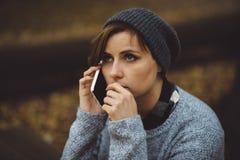 Porträt der traurigen Frau allein sitzend im Wald mit Smartphone Alleinbaum gegen Feld und Himmel mit Wolken Millenial, das Probl Lizenzfreies Stockbild