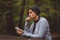 Porträt der traurigen Frau allein sitzend im Wald mit Smartphone Alleinbaum gegen Feld und Himmel mit Wolken Millenial, das Probl Stockfotografie