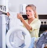Porträt der traurigen Hausfrau schmutzige Kleidung nehmend Stockfotos