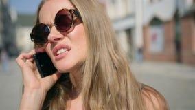 Porträt der Umkippenfrau sprechend am Telefon in einer Stadtstraße stock footage