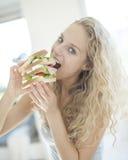 Porträt der ungeduldig Frau großes Sandwich im Haus essend Lizenzfreies Stockbild