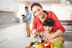 Porträt der unterrichtenden Tochter der glücklichen Mutter, zum des Gemüses zu schneiden Lizenzfreies Stockbild