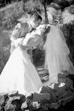 Porträt der verbiegenden Braut des Bräutigams vorbei und sie küssend Stockbild
