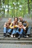 Porträt der vierköpfiger Familie sitzend im Park stockfotografie