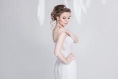Porträt der vorzüglichen und träumerischen jungen Braut im luxuriösen Spitzehochzeitskleid Stockfotos