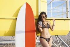Porträt der weiblichen Aufstellung des jungen glücklichen Surfers beim Fotografieren für Bild des Sozialen Netzes Lizenzfreies Stockfoto