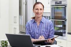 Porträt der weiblichen freiberuflich tätigen Arbeitskraft, die Laptop in der Küche an H verwendet Lizenzfreie Stockfotos