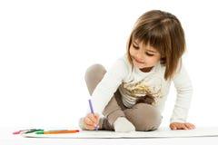 Zeichnung des kleinen Mädchens mit Wachszeichenstiften. Stockfotografie