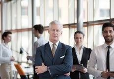 Porträt des älteren Geschäftsmannes als Führer mit Gruppe von Personen I Stockfoto
