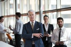 Porträt des älteren Geschäftsmannes als Führer mit Gruppe von Personen I Stockfotografie