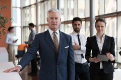 Porträt des älteren Geschäftsmannes als Führer mit Gruppe von Personen I Stockfotos