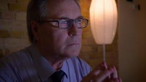 Porträt des älteren Geschäftsmannes in den aufpassenden Nachrichten des Kostüms im Fernsehen, die aufmerksam und nervös sind stock footage