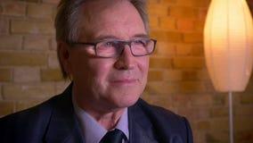 Porträt des älteren Geschäftsmannes im Kostüm und in den Gläsern Nachrichten im Fernsehen, aufpassend positiv und froh zu sein stock footage