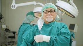 Porträt des älteren männlichen Chirurgen im Operationssaal stock video