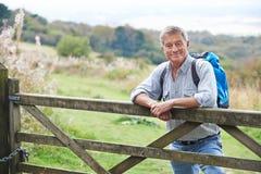 Porträt des älteren Mannes auf Wanderung in der Landschaft, die durch Tor stillsteht Lizenzfreies Stockfoto