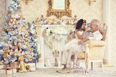 Porträt des älteren Mannes mit der Enkelin, die im Lehnsessel sitzt stockbild