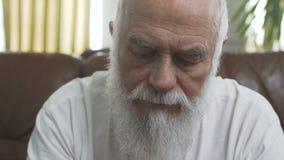 Porträt des älteren reifen alten bärtigen Mannes, der auf dem ledernen Sofa zu Hause isst Chips sitzt, schließen oben Großväterli stock footage