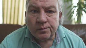 Porträt des älteren reifen alten Mannes mit den blauen Augen, die auf dem Sofa zu Hause Chips essend sitzen, schließen oben Großv stock video