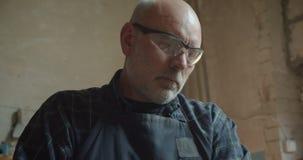 Porträt des älteren Tischlers in der Schutzgläserfunktion in der Fertigung, die konzentriert und ernst ist stock video footage
