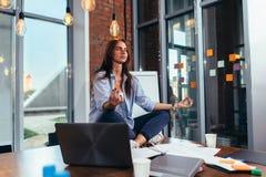 Porträt des übenden Yoga der attraktiven Geschäftsfrau, das auf Schreibtisch an ihrem Arbeitsplatz sitzt stockfotografie