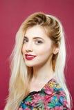 Porträt des Überraschens blond, die Kamera betrachtend und auf rosa Hintergrund im Studio lächelnd Lizenzfreie Stockbilder