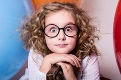Porträt des überraschten gelockten jugendlich Mädchens in den Gläsern auf dem backgrou Lizenzfreie Stockbilder