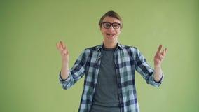 Porträt des überraschten jungen Mannes, der Gesicht im grünen Hintergrund berührend lächelt stock footage