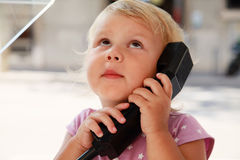 Porträt des überraschten kleinen Mädchens, das am Straßentelefon spricht Lizenzfreie Stockfotos
