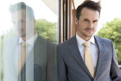 Porträt des überzeugten Geschäftsmannes lehnend auf Glastür lizenzfreie stockfotos