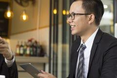 Porträt des überzeugten jungen Geschäfts, das bei Tisch beim Treffen im Freien, Geschäftsbericht in der Tablette und im Lächeln h Lizenzfreie Stockfotos