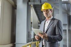 Porträt des überzeugten männlichen Architekten, der digitale Tablette in der Industrie hält stockfotos