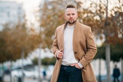 Porträt des überzeugten Mannes im braunen Mantel und in der weißen Strickjacke stockbild