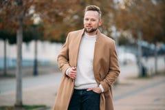 Porträt des überzeugten Mannes im braunen Mantel und in der weißen Strickjacke stockbilder