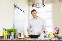 Porträt des überzeugten Mannes Lebensmittel in der Küche zubereitend Lizenzfreie Stockbilder