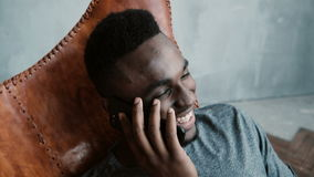 Porträt des afrikanischen Mannes sitzend im Stuhl in einem hellen Raum und auf Smartphone sprechend Mann, der Spaß lacht und hat Stockfotos