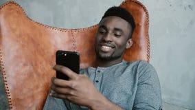 Porträt des afrikanischen Mannes sitzend im Stuhl und Smartphone verwendend Mann surft das Internet und lächelt Stockbilder