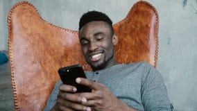 Porträt des afrikanischen Mannes sitzend im Stuhl, unter Verwendung Smartphones Mann liest Mitteilungen und lacht Schreibenmassag Stockfoto