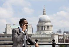 Porträt des Afroamerikanergeschäftsmannes sprechend am Handy in London Lizenzfreie Stockfotos