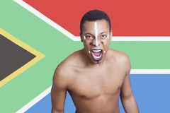 Porträt des aggressiven Mischrassemannes gegen südafrikanische Flagge Lizenzfreie Stockfotografie