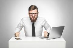 Porträt des aggressiven verärgerten jungen Chefs im weißen Hemd und Abendgarderobe sitzen im Büro und schlechte Stimmung habend,  stockbilder