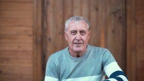 Porträt des alten Mannes sitzend auf dem Portal des Hauses Pensionär, der zur Kamera, zum Lächeln und zum Rauchen schaut 4K Lizenzfreies Stockbild
