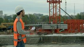 Porträt des amale Standort-Auftragnehmeringenieurs mit dem Sturzhelm, der Planpapier an der Baustelle hält stock video footage