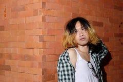 Porträt des androgynischen schönen jungen Mannes als Schönheit auf Backsteinmauerhintergrund Lizenzfreie Stockfotografie